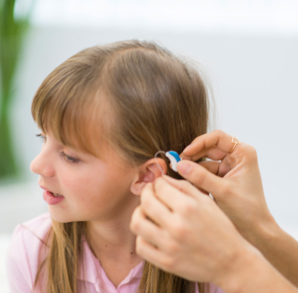 Helping deaf girl with hearing aid